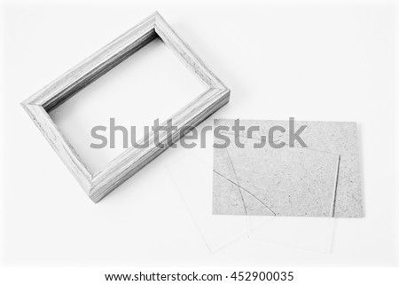 Wooden frame with broken glass on black and white background.