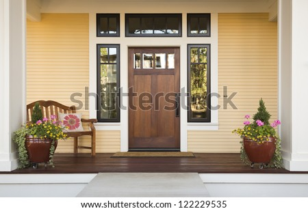 Wooden front door of a home. Front view of a wooden front door on a yellow house with reflections in the window and a wide view of the porch and front walkway. Horizontal shot. - stock photo