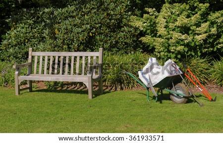 Wooden Garden Bench next To a Wheelbarrow with Garden Tools in a English Country Cottage Garden in Rural Devon, England, UK - stock photo