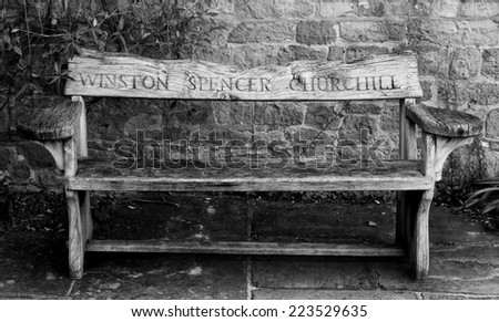 Wooden garden bench with the name Winston Spencer Churchill carved in the back from Chartwell House, Kent, his home until he died in 1965.  Against a stone wall on stone flagging.  Black and white . - stock photo