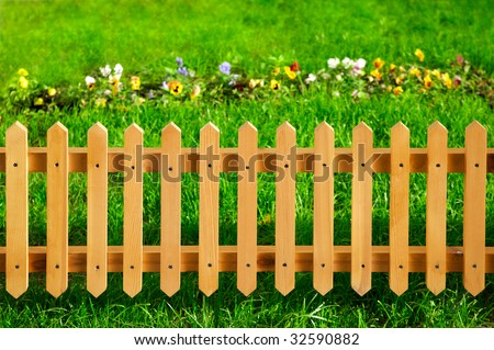 Wooden garden fence against green grass and flowers - stock photo