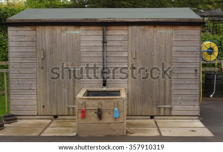 Wooden Garden Shed with a Hose Reel Attached at One End and Brushes for Cleaning Garden Tools in Devon, England, UK - stock photo