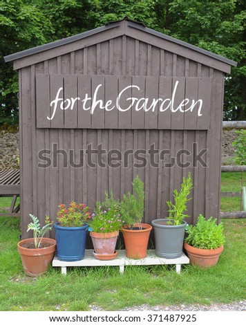 wooden garden shed with for the garden painted on the side with a row