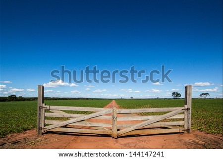 Wooden gate at farm closing the way - stock photo