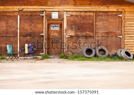 Wooden gate of rural timber building with closed sign and abandoned with two vacant chairs and old tires leaning against outside wall - stock photo