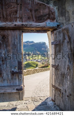 Wooden gates with an opened door leading to the mountains and nature park out of the castle.  Gutenberg castle in Liechtenstein.