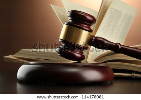 wooden gavel and book on wooden table, on brown background