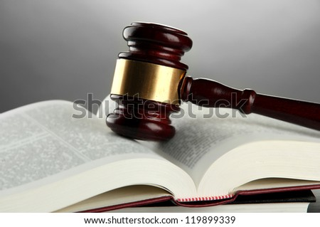 wooden gavel and books, on grey background - stock photo