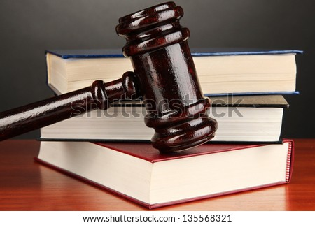 Wooden gavel and books on grey background