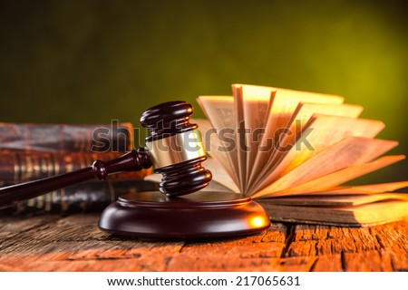 Wooden gavel and books on wooden table, law concept - stock photo