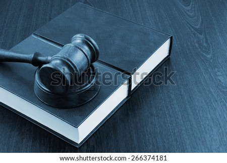 Wooden gavel and legal books on table - stock photo
