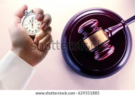 Wooden gavel, block and stopwatch in male hand