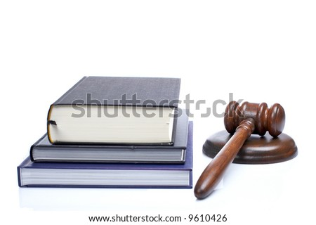 Wooden gavel from the court and law books reflected on white background. Shallow DOF - stock photo