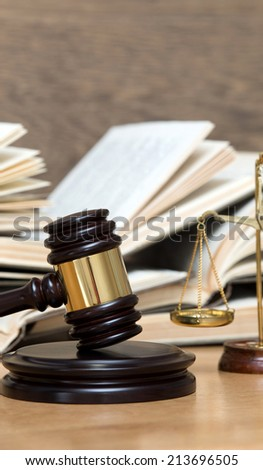 Wooden gavel, golden scales of justice and books on wood background - stock photo