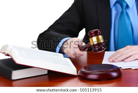 wooden gavel in hand and books on wooden table on gray background - stock photo