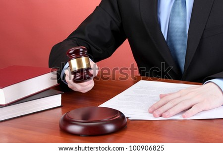 wooden gavel in hand and books on wooden table on red background - stock photo