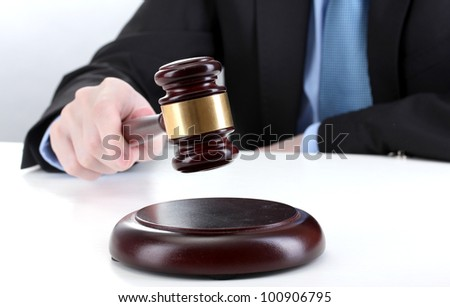 wooden gavel in hand on gray background - stock photo