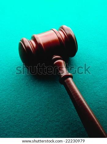 Wooden gavel on a green felt background - stock photo