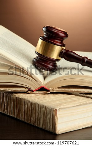 wooden gavel on books, on brown background - stock photo