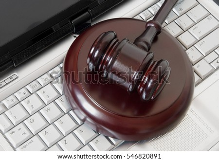 Wooden gavel on laptop computer, cyber law or crime concept