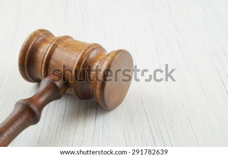 Wooden gavel on white table with room for text - stock photo