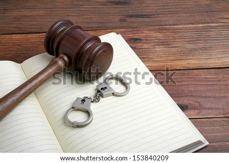 Wooden gavel, open book and handcuffs on wooden background - stock photo