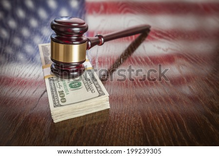 Wooden Gavel Resting on Stack of Money with American Flag Reflection on Table. - stock photo