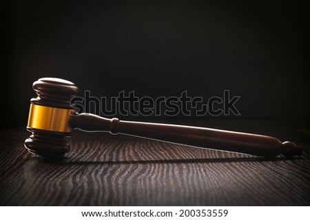 Wooden gavel with an ornamental brass band standing upright sideways on a textured dark wood surface conceptual of a judge or auctioneer - stock photo