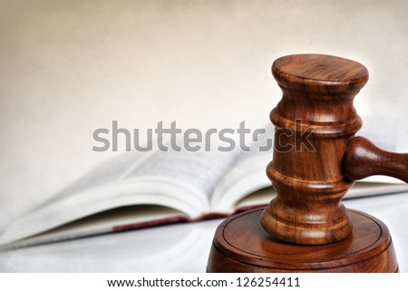 Wooden gavel with blurred law book behind.  Lots of copy-space. - stock photo