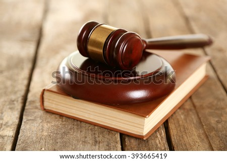 Wooden gavel with book on wooden background