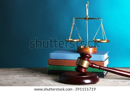 Wooden gavel with justice scales and books on blue background - stock photo