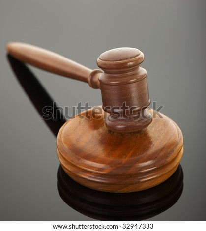 wooden gavel with reflection on black