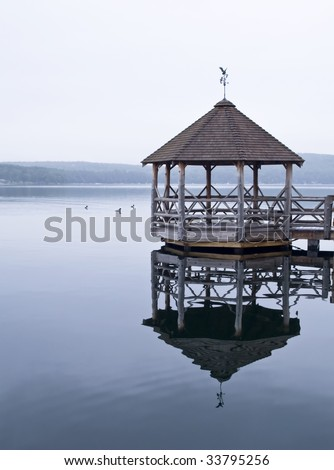 Wooden Gazebo located on the calm waters of a lake located in New Hampshire - USA - stock photo