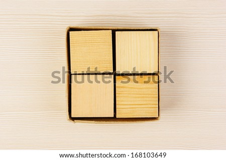 wooden geometric cube in a box - stock photo