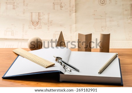 wooden geometric shapes and a notebook for recording - stock photo