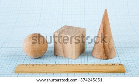 Wooden geometric shapes on graph paper