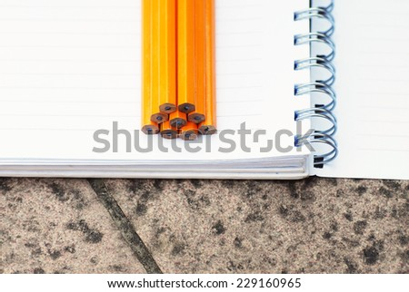 wooden graphite pencils on white open notebook closeup - stock photo