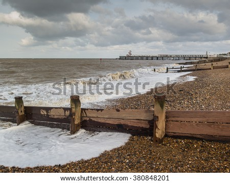 wooden groynes, water breakers on the pebble beach in Herne Bay, Kent, Uk, on a windy winter day. The pier can be seen on the horizon. - stock photo