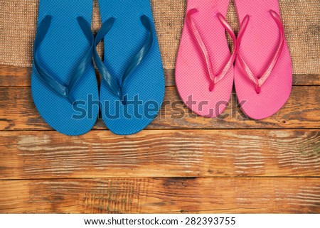 Wooden grunge background with two paar flip flop sandals - stock photo