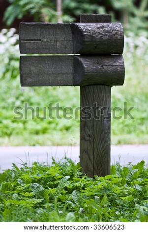 Wooden guide sign at a footpath in park - stock photo