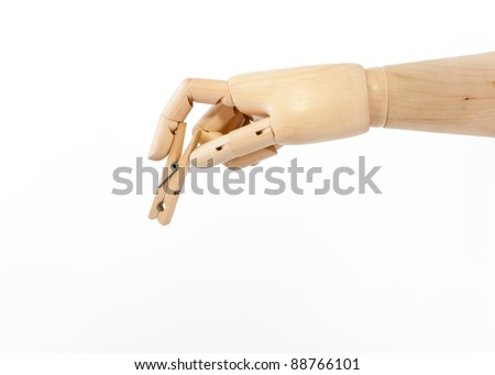 Wooden hand holding a clothes peg - stock photo