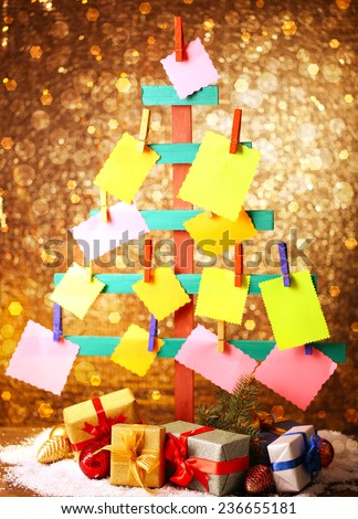 Wooden hand made fir tree with empty papers and Christmas decor on shiny background - stock photo