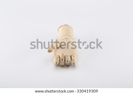 Wooden hand turned up on a gray background