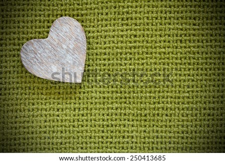 Wooden heart on a green fabric background with vignette - stock photo