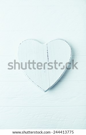 Wooden heart-shaped decoration on a white wooden surface