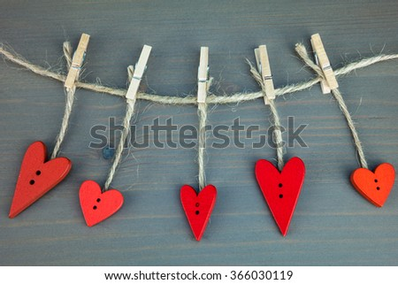 Wooden hearts on clothespins on grey wooden background. Post card for the Valentine. Button love. Wooden buttons. Valentine's Day postcard. - stock photo