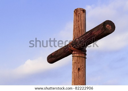Wooden High Cross with blue sky and a few white clouds above a green landscape - stock photo