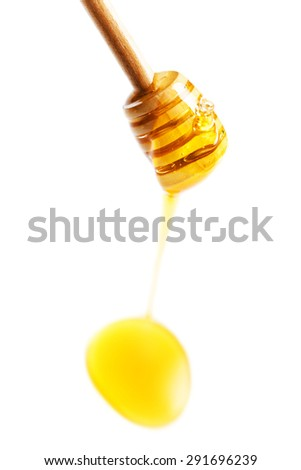 Wooden honey dipper with yellow honey flowing drops  isolated on white background macro.  - stock photo