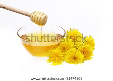 Wooden honey drizzler with honey and healthy dandelion honey on white background
