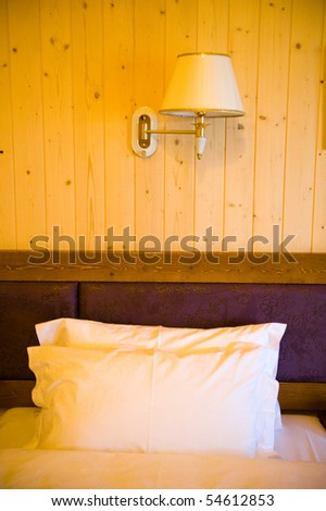 Wooden hotel room with bed , and lamp on the wall. - stock photo